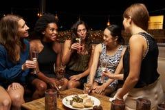 Grupo de amigos femeninos que disfrutan de noche hacia fuera en la barra del tejado Fotos de archivo