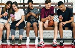 Grupo de amigos jovenes del adolescente en una cancha de básquet Imagen de archivo libre de regalías