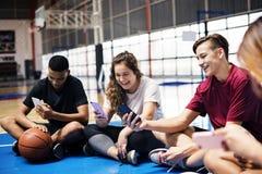 Grupo de amigos jovenes del adolescente en una cancha de básquet que relaja y que usa smartphone Imágenes de archivo libres de regalías