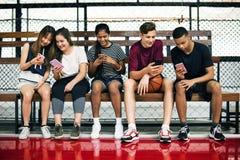 Grupo de amigos jovenes del adolescente en una cancha de básquet que se relaja usando smartphone Imagenes de archivo