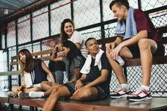 Grupo de amigos jovenes del adolescente que se sientan en un banco que se relaja Fotografía de archivo