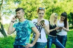 Grupo de amigos jovenes del inconformista que usan el teléfono elegante con desinterés en uno a Foto de archivo libre de regalías