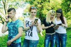 Grupo de amigos jovenes del inconformista que usan el teléfono elegante con desinterés en uno a Foto de archivo