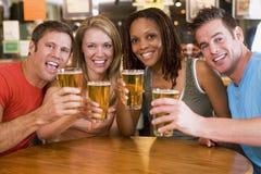 Grupo de amigos jovenes en barra que tuestan la cámara Foto de archivo libre de regalías