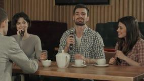 Grupo de amigos jovenes en el partido que canta en el club del Karaoke Imagen de archivo libre de regalías