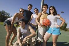 Grupo de amigos jovenes en la cancha de básquet. Foto de archivo libre de regalías