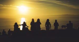 Grupo de amigos jovenes en salida del sol del océano de la playa del fondo, danzas románticas de la gente de la silueta que miran foto de archivo