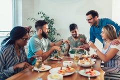 Grupo de amigos jovenes felices que disfrutan de la cena en casa fotografía de archivo
