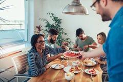 Grupo de amigos jovenes felices que disfrutan de la cena en casa imagen de archivo libre de regalías