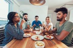 Grupo de amigos jovenes felices que disfrutan de la cena en casa imágenes de archivo libres de regalías