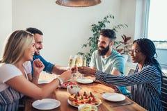 Grupo de amigos jovenes felices que disfrutan de la cena en casa imagenes de archivo
