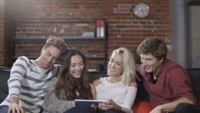 Grupo de amigos jovenes felices que se sientan en un sofá que comparte una tableta almacen de metraje de vídeo