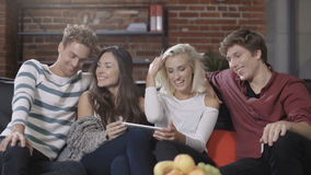 Grupo de amigos jovenes felices que se sientan en un sofá que comparte una tableta almacen de video
