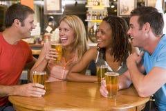 Grupo de amigos jovenes que beben y que ríen Imágenes de archivo libres de regalías