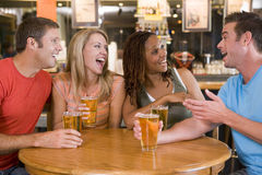 Grupo de amigos jovenes que beben y que ríen Fotos de archivo