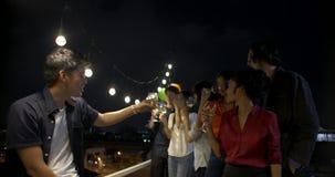 Grupo de amigos jovenes que celebran festival del Año Nuevo y de la Navidad junto en el tejado del verano