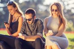 Grupo de amigos jovenes que charlan por los teléfonos Fotografía de archivo