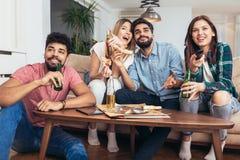 Grupo de amigos jovenes que comen la pizza y que ven la TV imagen de archivo libre de regalías