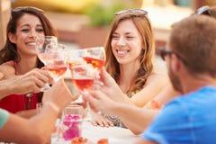 Grupo de amigos jovenes que disfrutan de la comida en restaurante al aire libre foto de archivo