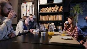 Grupo de amigos jovenes que gozan en café junto metrajes