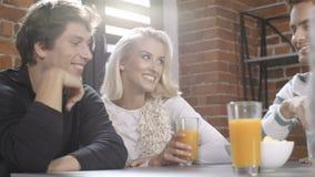 Grupo de amigos jovenes que hablan alrededor de una tabla con las bebidas anaranjadas sanas en un día del ocio en interior modern almacen de metraje de vídeo