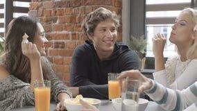 Grupo de amigos jovenes que hablan alrededor de una tabla con las bebidas anaranjadas sanas en un día del ocio en interior modern almacen de video