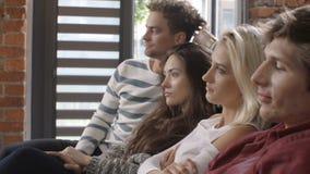 Grupo de amigos jovenes que miran la televisión junto en el sofá almacen de metraje de vídeo