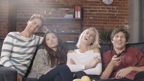 Grupo de amigos jovenes que miran la televisión junto en el sofá en interior moderno del desván metrajes