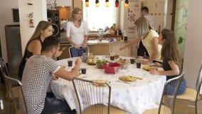 Grupo de amigos jovenes que recolectan en el cuarto dinning que tiene junto una comida del ocio de la comida del almuerzo y un co almacen de metraje de vídeo