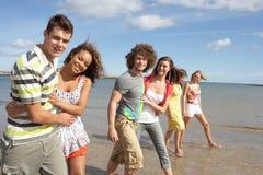 Grupo de amigos jovenes que recorren a lo largo de línea de la playa Fotografía de archivo