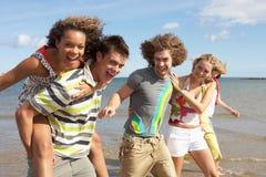 Grupo de amigos jovenes que recorren a lo largo de línea de la playa Imagen de archivo libre de regalías