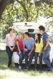 Grupo de amigos jovenes que se sientan en el tronco del coche Imagenes de archivo