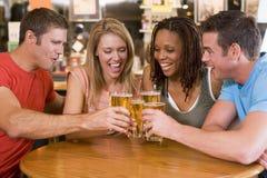 Grupo de amigos jovenes que tuestan en una barra Imagen de archivo libre de regalías