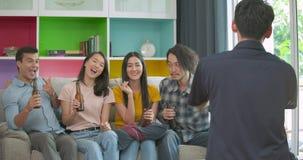 Grupo de amigos jovenes que van de fiesta y que gozan a tomar la foto en el sofá junto en casa almacen de metraje de vídeo