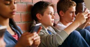 Grupo de amigos de la escuela que usan el teléfono móvil 4k metrajes