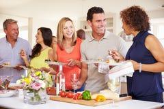 Grupo de amigos maduros que apreciam o bufete no partido de jantar imagens de stock