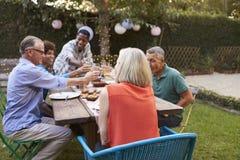 Grupo de amigos maduros que disfrutan de la comida al aire libre en patio trasero imagenes de archivo