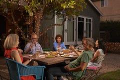 Grupo de amigos maduros que disfrutan de la comida al aire libre en patio trasero fotografía de archivo