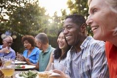 Grupo de amigos maduros que disfrutan de la comida al aire libre en patio trasero imagen de archivo libre de regalías