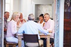 Grupo de amigos maduros que disfrutan de la comida en casa junto imágenes de archivo libres de regalías