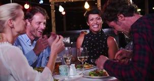 Grupo de amigos maduros que disfrutan de la comida en el restaurante del tejado almacen de metraje de vídeo