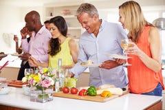 Grupo de amigos maduros que gozan de la comida fría en el partido de cena fotografía de archivo libre de regalías