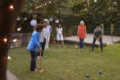 Grupo de amigos maduros que jogam o cróquete no quintal junto fotos de stock royalty free