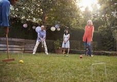 Grupo de amigos maduros que juegan el croquet en patio trasero junto imagenes de archivo