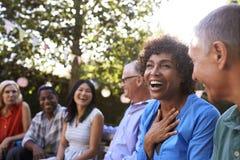 Grupo de amigos maduros que socializan en patio trasero junto foto de archivo