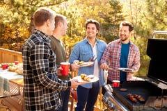 Grupo de amigos masculinos alegres que apreciam o assado junto fotografia de stock
