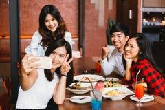 Grupo de amigos masculinos e fêmeas asiáticos felizes que tomam uma foto do selfie e que comem um brinde social junto no restaura imagens de stock royalty free
