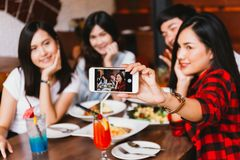 Grupo de amigos masculinos e fêmeas asiáticos felizes que tomam uma foto do selfie e que comem um brinde social junto no restaura foto de stock