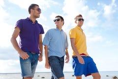 Grupo de amigos masculinos que caminan en la playa Imagenes de archivo