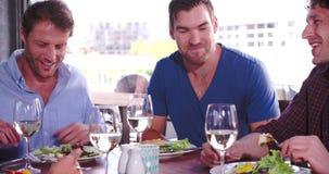 Grupo de amigos masculinos que disfrutan de la comida en restaurante junto almacen de metraje de vídeo